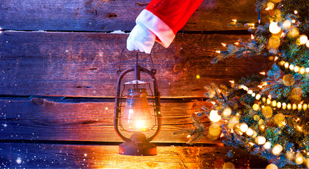Christmas scene. Santas hand holding vintage oil lamp over wooden background Stock Photo