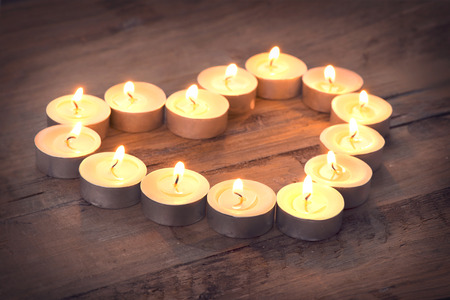 saint valentine   s day: Valentine`s Day Heart shaped Candles. Valentine Heart of candles on wooden background. Beautiful Valentines Vintage Background Stock Photo