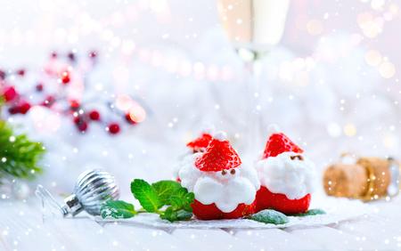 Christmas strawberry Santa. Funny dessert stuffed with whipped cream. Xmas party food idea Stock Photo