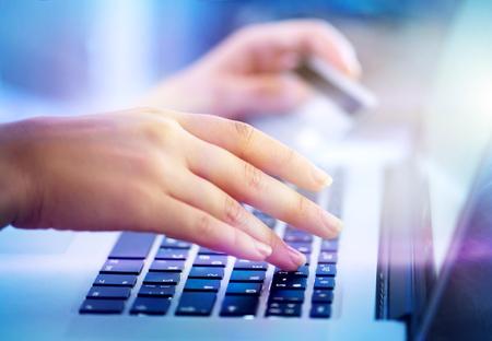 tecla enter: manos de la mujer joven que sostiene la tarjeta de crédito y equipo portátil para compras en línea, la banca electrónica