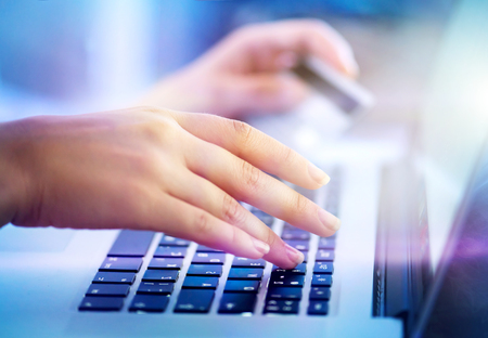 Young woman hands holding credit card and using laptop computer for online shopping, e-banking Stock Photo