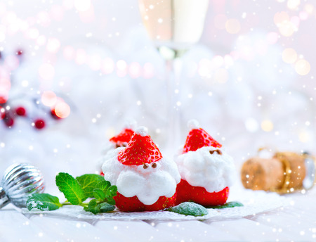 Christmas strawberry Santa. Funny dessert stuffed with whipped cream. Xmas party food idea Фото со стока