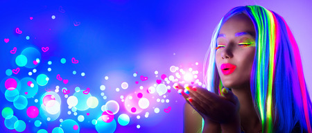Valentine's Day girl on disco party. Fashion model woman in neon light, blowing Valentine neon hearts