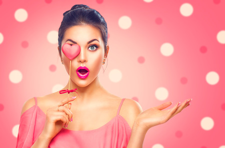 Valentines Day. Beauty surprised young fashion model girl with Valentine heart shaped cookie Фото со стока