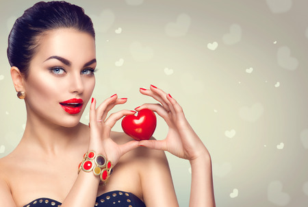 face to face: Fashion woman with red heart. Valentines day art portrait. Beautiful makeup and manicure