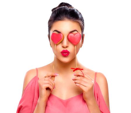 バレンタインの日。彼女の手でバレンタイン ハート型クッキーとうれしそうな若者のファッション モデル美少女