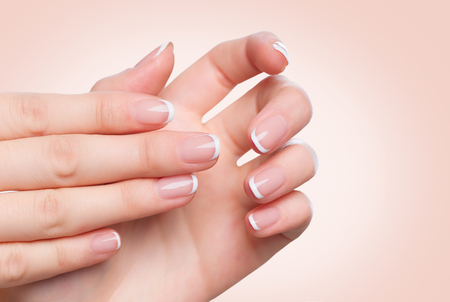 aging: Female hands with french manicure. Spa and skincare concept