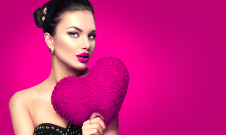 Sexy Valentine model girl portrait. Gorgeous Valentines young brunette woman with heart shaped purple pillow on pink background