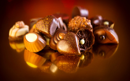 Assorted chocolate candies over golden background. Heart shaped chocolate