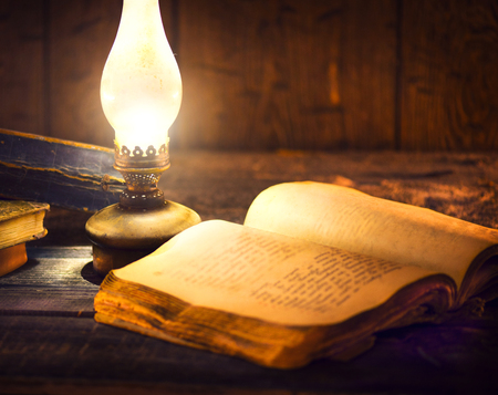 aged: Old books and vintage oil lamp. Kerosene lantern and open old book on wooden table