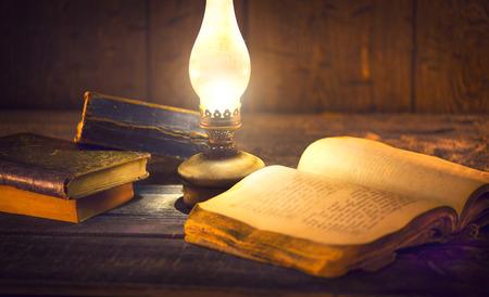 古い書籍やビンテージ オイル ランプ。灯油ランタンと木製のテーブルに開かれた古い本 写真素材