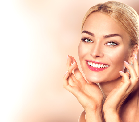 Beauty woman portrait. Beautiful spa girl touching her face and smiling. Perfect fresh skin Stock Photo