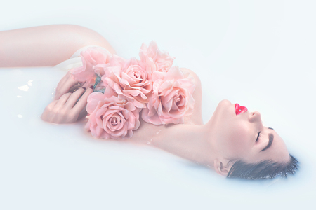 salon and spa: Beautiful fashion model girl with bright makeup and pink roses taking milk bath, spa and skin care concept Stock Photo