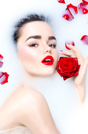 woman in bath: Beauty young model girl with bright makeup and red rose flower relaxing in milk bath Stock Photo