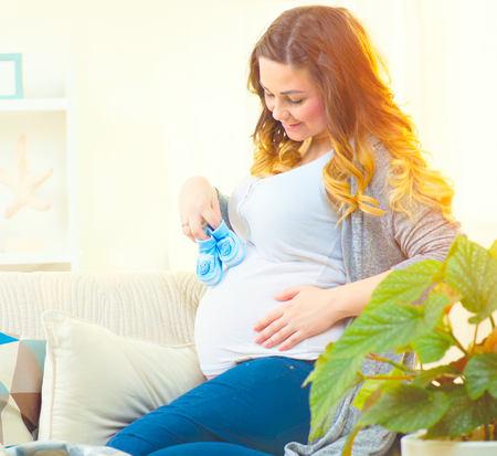 healthy body: Pregnant happy woman holding blue baby shoes in her hands Stock Photo