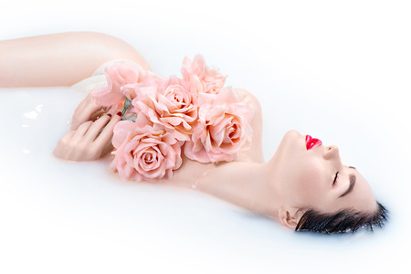aged: Beautiful Fashion model girl with bright makeup and pink roses taking milk bath, spa and skin care concept