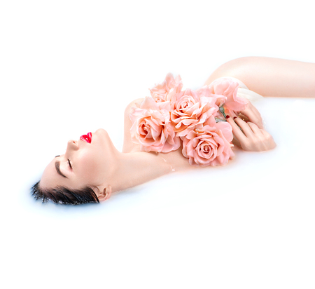 Beauty young model girl with bright makeup and pink roses relaxing in milk bath
