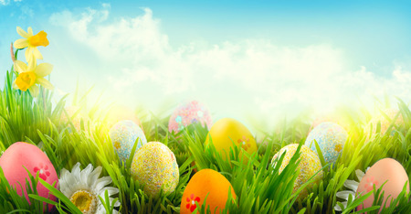 Easter nature spring scene background. Beautiful colorful eggs in spring grass meadow