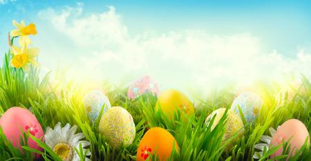 Pasen natuur lentescène achtergrond. Mooie kleurrijke eieren in het voorjaar gras weide Stockfoto