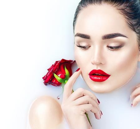 bath: Beautiful fashion model girl taking milk bath, spa and skincare concept