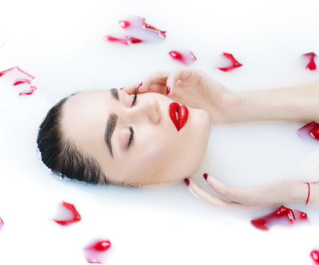 Beautiful fashion model girl taking milk bath, spa and skincare concept