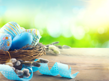 decoration: Easter colorful painted eggs with spring flowers and blue satin ribbon on wooden table top background