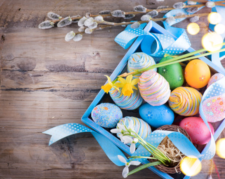 table top: Easter colorful painted eggs with spring flowers and blue satin ribbon on wooden table top background