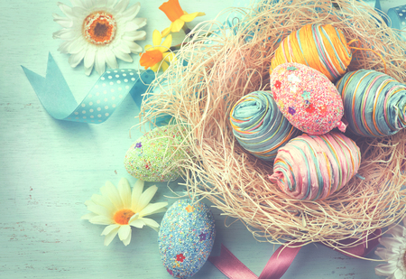 retro: Easter colorful eggs with decorations over blue wooden background