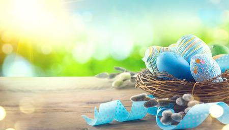 Pasen kleurrijke geschilderde eieren met lente bloemen en blauw satijn lint op houten tafelblad achtergrond