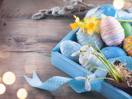 happy holidays: Easter colorful painted eggs with spring flowers and blue satin ribbon on wooden table top background