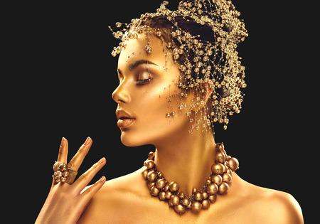 Gold vrouw huid. Schoonheid fashion model meisje met gouden make-up, haar en sieraden op zwarte achtergrond