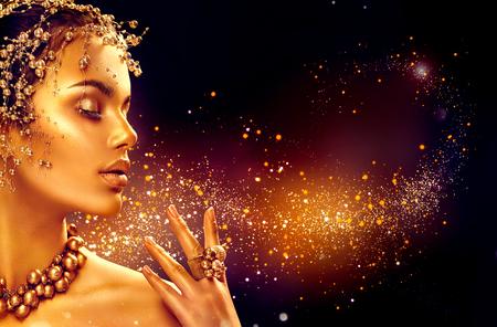 Peau femme d'or. mannequin de beauté fille avec le maquillage d'or, des cheveux et des bijoux sur fond noir Banque d'images - 72743013