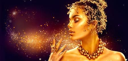 amarillo y negro: piel de la mujer de oro. chica modelo de manera de la belleza con oro de maquillaje, el pelo y joyas sobre fondo negro Foto de archivo