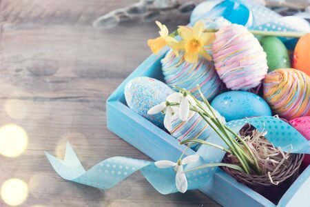 greeting season: Easter colorful painted eggs with spring flowers and blue satin ribbon on wooden table top background