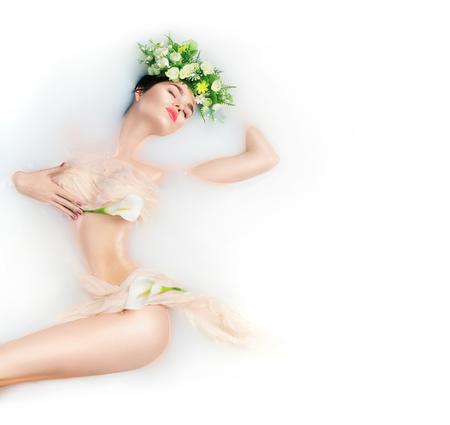 牛乳風呂、スパ、スキンケアの概念を取っている美しいファッション モデル女の子