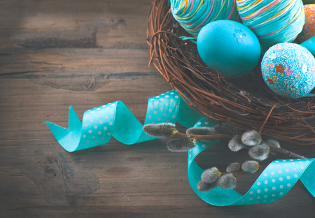 Easter colorful painted eggs with spring flowers and blue satin ribbon over wooden background