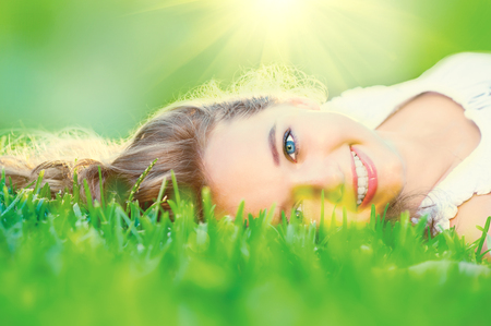 Beautiful teenage girl lying on green grass outdoor photo