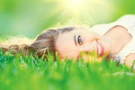 Beautiful teenage girl lying on green grass outdoor