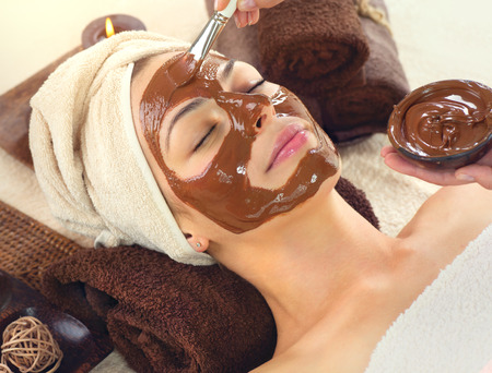 salon and spa: Chocolate Spa. Beautiful young woman relaxing in spa salon, applying chocolate face mask