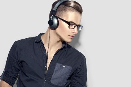 salon: Handsome young man enjoying music on headphones. Model guy in black shirt