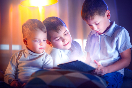 online: Three little boys with tablet computer in a dark room. Kids playing games on tablet pc Stock Photo
