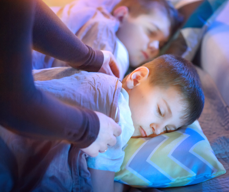 Children sleeping and dreaming in bed. Mother cover her little sons with a blanket photo