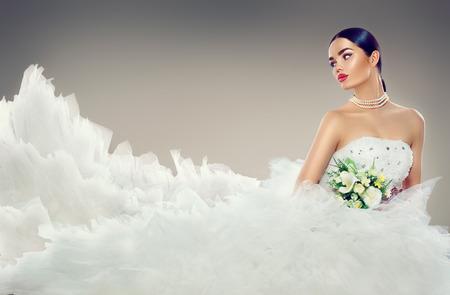 긴 기차 웨딩 드레스에서 뷰티 모델 신부. 우아한 흰색 웨딩 드레스 아름다운 약혼녀