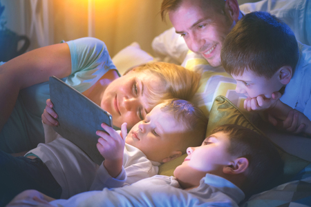 Happy family together watching movie on tablet computer in dark room Banco de Imagens - 75051236