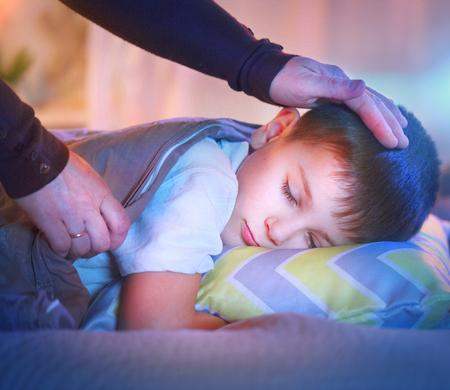 Niño pequeño que duerme y soñando en su cama. Madre cubre su pequeño hijo con una manta Foto de archivo - 75051232