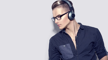 music background: Handsome young man enjoying music on headphones. Model guy in black shirt