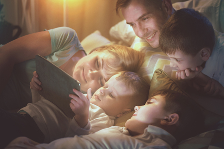 large: Happy family together watching movie on tablet computer in dark room