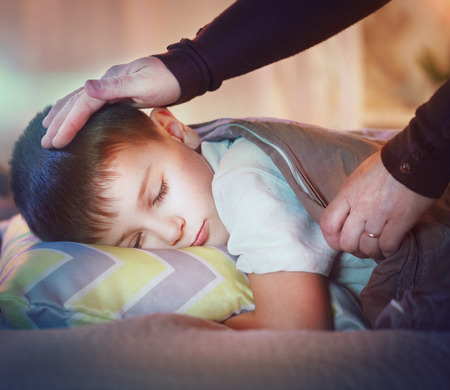 Little boy sleeping and dreaming in his bed. Mother cover her little son with a blanket Stock Photo