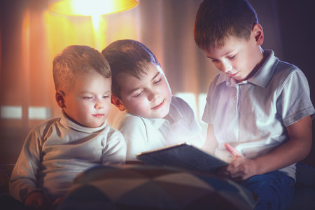 Three little boys with tablet computer in a dark room. Kids playing games on tablet pc photo