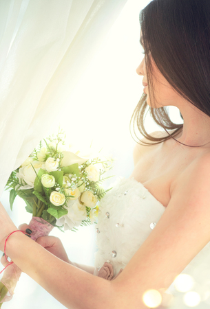 Beauty fashion young model bride in wedding white dress holding bouquet